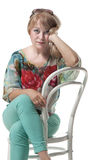 Blonde sits on a chair Royalty Free Stock Photos