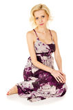 Blonde sits in a dress Royalty Free Stock Image
