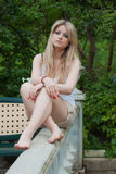 Blonde sits in a park Royalty Free Stock Photography