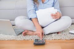 Blonde sitting on carpet using calculator Stock Photo