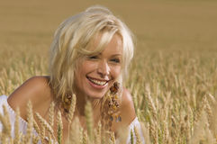 Blonde sitting on a field of wheat Stock Photo