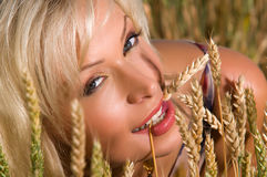 Blonde sitting on a field of wheat Royalty Free Stock Photo