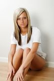 Blonde sitting on floor Stock Photography