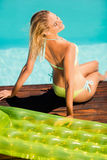 Blonde sitting on pools edge Stock Photos