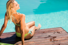 Blonde sitting on pools edge Stock Photography