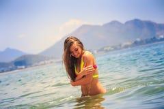 blonde slanke vrouwelijke turner in bikinitribunes in zeewater Stock Foto's