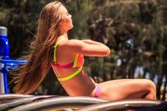 Blonde slim girl in bikini does bending of body on arch ladder Royalty Free Stock Image