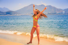 Blonde slim girl in bikini expresses joy jumps tip toe on sand. Blonde slim female gymnast in bikini expresses joy jumping on tip toe on beach wind shakes hair royalty free stock images
