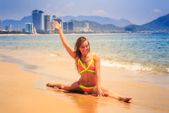 blonde slim girl in bikini makes split on wet sand smiles at sea Royalty Free Stock Photos