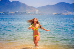 Blonde slim girl in bikini poses in shallow sea water smiles Royalty Free Stock Photos