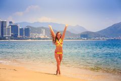 Blonde slim girl in bikini poses on tip toe on beach. Blonde longhaired slim female gymnast in bikini poses barefoot on tip toe on azure sea edge against resort royalty free stock image