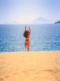 Blonde slim girl in bikini runs from sea on sand laughs Stock Photos