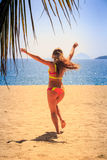 Blonde slim gymnast in bikini backside runs to sea hands up Stock Images
