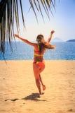 Blonde slim gymnast in bikini backside runs to sea hands up Stock Images