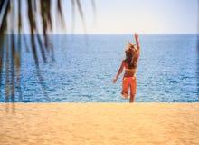 Blonde slim gymnast in bikini backside runs to sea waves hand Royalty Free Stock Image