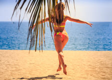 Blonde slim gymnast in bikini backside view jumps over sand Stock Image
