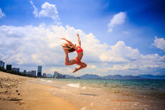 Blonde slim gymnast in bikini in jump over beach against sky Stock Photo