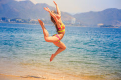 Blonde slim gymnast in bikini in jump over sea against hills Royalty Free Stock Image