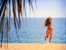 Blonde slim gymnast in bikini side view runs to sea smiles Stock Photos