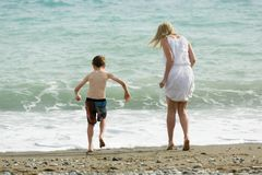 Blonde slim mother and her child enjoy together summer, waves of sea at beach. stock image