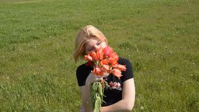 The blonde smells a bouquet of tulips. Girl with a bouquet of tulips flowers.  stock video footage