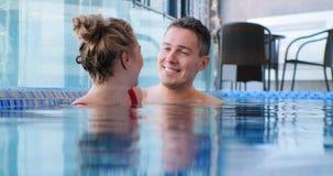 Blonde smiles submerged in blue swimming pool water near man