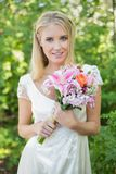 Blonde smiling bride holding bouquet looking at camera. In the countryside stock images