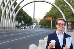 Blonde smiling businesswoman with glasses holding disposable cup in empty city street with copy space Royalty Free Stock Photography