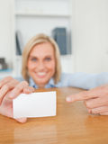 Blonde smiling businesswoman pointing at a card Stock Images