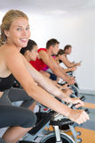 Blonde smiling at camera during spin class Royalty Free Stock Photography