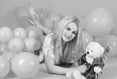 Blonde on smiling face relaxing with teddy bear toy. Girl in pajama, domestic clothes lay near air balloons, pink