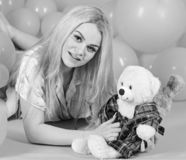 Blonde on smiling face relaxing with teddy bear toy. Woman cute celebrate birthday with balloons. Girl in pajama