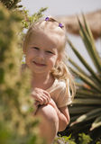 Blonde smiling girl. Portrait of blonde funny smiling girl sitting in park plants royalty free stock photography