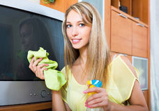 Blonde smiling girl cleaning TV Stock Image