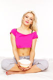 Blonde smiling girl holding bowl. After breakfast , wearing pink top , sitting on a bed cover in studio royalty free stock image