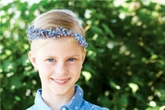 Blonde smiling girl is in a wreath of blue forget-me Stock Photos