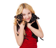 Blonde smiling little girl holding two puppies Stock Images