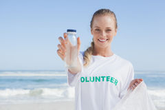 Blonde smiling volunteer picking up trash on the beach Royalty Free Stock Photography