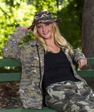 Blonde smiling woman in camouflage. Standing on a bench Stock Photography