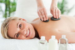 Blonde smiling woman experiencing a stone therapy Stock Photography