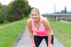 Blonde smiling woman resting after running. Blonde smiling woman holding knees after jogging along river Royalty Free Stock Photography