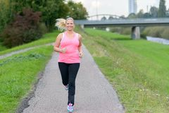 Blonde smiling woman running along river. Front view of blonde smiling woman wearing sportswear running along river Royalty Free Stock Photos