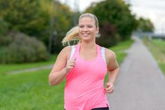 Blonde smiling woman running along river. Front view of blonde smiling woman wearing sportswear running along river, close up Royalty Free Stock Images