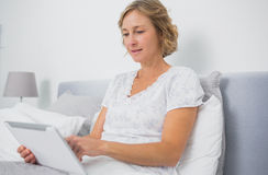 Blonde smiling woman sitting in bed using tablet pc Stock Photos