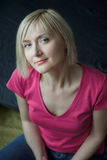 Blonde smiling woman wearing fuchsia color shirt vertical portrait. Blonde smiling woman is wearing fuchsia color shirt vertical portrait royalty free stock photo