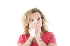 Blonde sneezing. Young blond girl sneezing in the handkerchief in front of the white background Stock Photo
