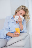 Blonde sneezing on tissue and holding glass of orange juice Stock Image