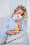 Blonde sneezing on tissue and holding glass of orange juice Stock Image