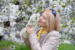 The blonde sniffs a flower Royalty Free Stock Photo