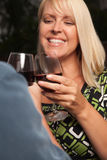 Blonde Socializing with Wine Glass. Wine Drinking Blonde Socializing with Man at an Evening Gathering Stock Image